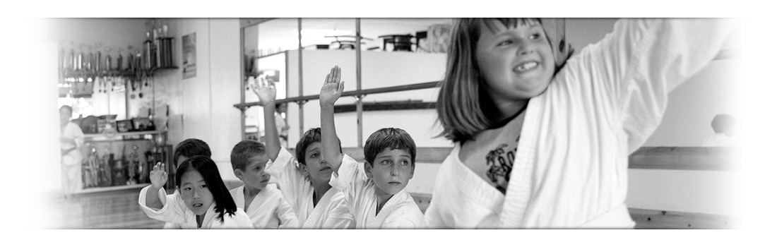 Children in Gis sit in a line on the dojo floor
